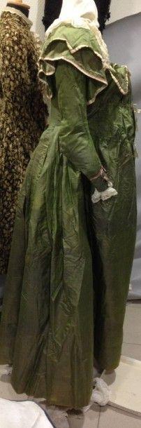 Rare robe redingote modifiée pour accommoder la grossesse, vers 1790. Taffetas de soie. Manteau à dos baleiné à l'anglaise et plis marqués, double col châle souligné d'un galon en taffetas Chiné à la branche. Corps intérieur souple à lacer, terminé en pointe sur le devant à basques découpées et galonnées de satin rayé. «Sur-robe» réunie aux côtés du corsage baleiné avec taille et décolleté ajustables sur 3 hauteurs différentes par des rubans de soie passées dans des fronces