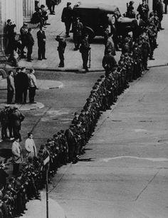 """Am Sonntag, den 13. August 1961, riegeln Grenzpolizisten, Volkspolizisten, Mitglieder der """"Kampfgruppen der Arbeiterklasse"""" und Soldaten der NVA die Sektorengrenze nach West-Berlin und den Berliner Außenring ab. Überall werden Straßen aufgerissen, Panzersperren und Stacheldrahtverhaue errichtet. In den folgenden Tagen beginnen Bautrupps unter Bewachung damit, den Stacheldraht durch eine circa zwei Meter hohe Mauer zu ersetzen, die Berlin in zwei Hälften zerschneidet. (Text-gekürzt: hdg.de)"""