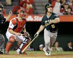 Oakland Athletics John Jaso, right, watches his three run home run as Los Angeles Angels catcher Chris Iannetta looks on during the seventh inning of a baseball game in Anaheim, Calif. Tuesday, April 9, 2013.