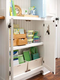 Organize & Hide  Cabinets in the hallway near the kitchen house office supplies. A bamboo stationery holder, stacking flip-top bins, and an acrylic organizer stash small items such as paper clips, pens, and computer cords, while larger canvas bins hold notepads, printer paper, file folders, and gift-wrapping supplies.