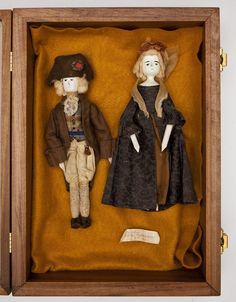"""DESCRIPTION: George and Martha Washington wooden dolls in wood case. Each with painted face and simplistic arms and legs. George is dressed in a colonial hat with rosette and matching brown jacket with tan knickers and knit socks. Martha is dressed in a gold, brown, and blue gown with a bonnet and ribbon covering her head. Case lined with orange felt. 19th century. MEASUREMENTS: George 9-1/2"""" long. Martha 9"""" long. Case 14-5/8"""" x 10-1/2"""" x 3-1/4"""" deep."""