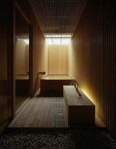 A traditional hinoki (cypress wood) tub for soaking.  Designed by Kengo Kuma for Fujiya inn, Yamagata.  The wooden slatted area in the foreground is for washing before entering the tub.