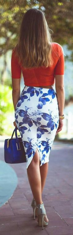 Falda de flores azules, blusa naranja. Bolso azul.