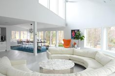 A curved sofa encircles a marble-topped coffee table in this spacious, light-filled living room. The large sofa provides seating for a crowd while keeping with the modern, streamlined look of the space.