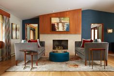 A pair of gray velvet, tufted sofas and a low, blue ottoman form a comfy seating area next to the fireplace in this lovely, midcentury modern living room. The blue accent wall sets the tone for the color palette, with punches of red found in the throw pillows and curtains.