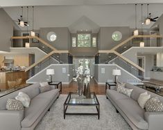 Symmetrical living room, large open floor plan, double stairways, gray couches | Spacecrafting / Architectural Photography