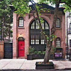 Mais tradicional, esta casa apostou nos tijolos tom terra e no estilo industrial, com janelas pretas e uma porta vermelha.