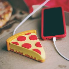 "Holy shit! Is it a pizza? Is it a charger? It's both and now you can charge your phone with your favorite food. Dimensions: 3 1/2"" x 4 1/2"" x 1 1/2"" Battery Capacity: 2,600 mAh Device charges iOS & An"