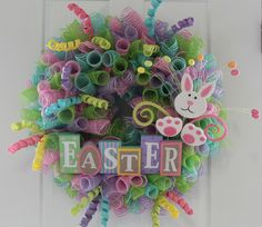 """All the colors of Easter displayed on your front door. Follow along and see a unique technique for crafting the DIY Mesh Easter wreath.You need just a few supplies:4 Rolls of 10""""Deco Mesh. Each in a different color.16"""" Work Wreath2 Curly Easter Floral Picks1 Easter Bunny PickWooden Easter SignFloral WireThe first thing you will do is cut the mesh in 12"""" pieces. A quick way to do this is roll all 4 rolls layering themon top of each other.Cut the entire roll of ea..."""