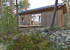 Lake cabin by Sini Kamppari features slatted timber walls and a projecting terrace.
