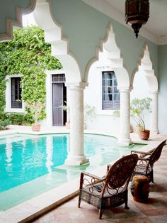 Outdoor pool and patio with Moroccan inspired architecture seen in archways and columns.