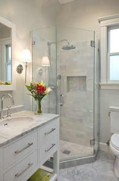 Small white bathroom with marble tile, white cabinets, glass shower doors,  flowers. Small Bathroom Ideas: Shower Spaces from Bathroom Bliss by Rotator  Rod