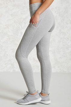 An athletic pair of stretch heathered knit leggings featuring dual side pockets with mesh inserts, a flatlock rise, moisture management, and a hidden key pocket in the waistband.