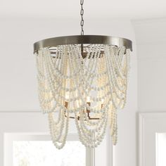 Eye-catching drama for your dining room, entryway or master bedroom. Our Andrea Chandelier is handmade with hundreds of white clay beads hung in graceful overlapping drapes from an antique brass crown. Light peeks through the draped beading to create a warm ambient glow. This beautiful 4 light candle cluster chandelier makes a beautiful entry way chandelier, dining room light, or over the bed chandelier.  #Chandelier #Lighting #EntryChandelier Entry Chandelier, Beaded Chandelier, Chandelier Pendant Lights, Chandeliers, Kitchen Lighting Design, Kitchen Lighting Fixtures, Dining Room Lighting, Bedroom Light Fixtures, Floral Bedding