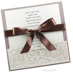 CHOCOLATE CRACKLE  This wedding invitation is simple but beautiful. It features a Urban Mocca backing card and an Ivory Pebbles pocket The insert simply slides into the pocket and it is all finished with a beautiful chocolate brown satin ribbon with bow. Your RSVP card and envelopes can also slip into the pocket behind the insert. Price: $4.95 https://www.facebook.com/NextChapterWeddingInvitations