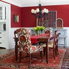 Red dining room. Brown table. Like the idea of having patterned, cushion seats on the ends. Also like having an oriental rug. And the random wood/glass pieces on the wall. Greenery in the middle is nice.
