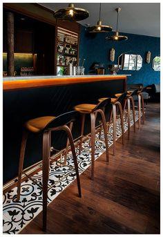La barra de madera contrasta con el piso y muros texturizados.