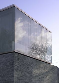 Full height glass on solid base; Casa Burren / Níall McLaughlin Architects Sky and trees reflect in the glass