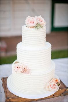 three tiered white wedding cake with pink rose