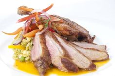 ARROZ CON PATO - a gourmet version of an iconic Peruvian dish with duck served two ways: crispy duck confit and duck breast  pan-seared to order, paired with cilantro-infused rice, a savory-sweet passionfruit sauce and baby carrots  Photo by Alyson Levy