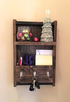 The amazing entryway shelf functions as a shelf, key holder, coat rack and mail organizer. It is made from reclaimed wood (pine) that has been stained a dark walnut. This piece will look great in an entryway, kitchen, bathroom or any room in your house! It has 3 hooks great for hanging keys and hats. There is a compartment for pens, pencils and scissors. It measures 12x 19. This shelf will add a little rustic charm to any home