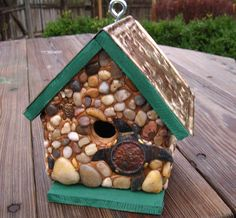 """Turtle Bay Cedar birdhouse with stones and river rock collected from the shores of Lake Michigan, local rivers and from creek beds and recycled embellishments of two metal turtles. Roof and base is weatherproof stained in forest green and roof has a embossed faux antique gold tone tile. Suitable for outdoor or indoor décor. Removable base for easy clean out.          1 1/4"""" opening   $56.00 plus shipping"""