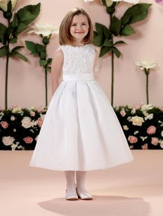 This precious dress is ideal as a First Holy Communion dress.  The sleeveless satin, organza and lace tea-length A-line girl's dress has a jewel neckline, sequin lace overlay bodice accented with three-dimensional hand-beaded flowers and covered buttons.