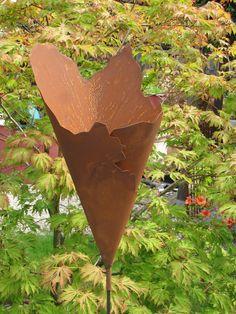 Edelrost Metalltüte Fackel  Schöne, rustikale Metalltüte in Edelrost, die auf einem 120 cm Stab geliefert wird. Die Tüte läßt sich schön bepflanzen oder kann auch mit einer Brenngeldose wunderbar beleuchtet werden.  Größe:  Höhe: 50 cm + 120 cm Stab Durchmesser unterer Rand: 22 cm Durchmesser oberer Rand: 26 cm