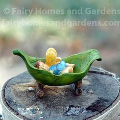 A tiny woodland knoll fairy baby sleeps sweetly in a rocking cradle fashioned from a leaf.