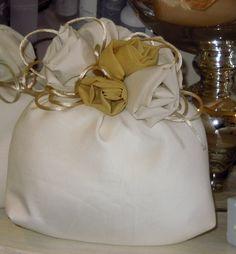 Saccotto seta con rose gialle e avorio fatte a mano.  Dimensione: 20x18 cm.  Completa di n.5 confetti incartati e avvolti nel tulle.