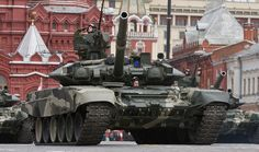 A Russian T-90 tank crew driving their vehicle through Red Square as part of 2014 Victory Day celebrations.