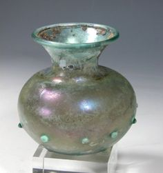 """Beautiful color and form! Ancient Roman Glass Jar, ca. 100 - 300 A.D. Pale translucent blue-green glass vessel with interesting small nodules evenly spaced about 1"""" apart all around the bulbous midsection. Nicely-flared opening with rolled rim. Beautiful iridescence with accents of red, purple, gold, more! 3-1/4""""H, intact/generally excellent, save stable internal crack along base #antique"""