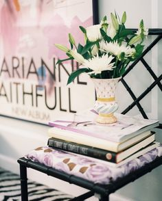 Chair - A stack of books and a vase atop a black fretwork chair