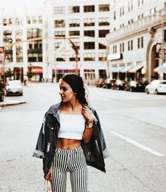 Black and white striped high waisted skinny jeans pants with white tube top crop top and large oversized black distressed jean jacket for women's edgy spring style inspiration