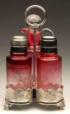 "CYLINDER - CREASED NECK THREE-PIECE CONDIMENT SET, rubina, comprising a salt and pepper shaker with matching period two-part lids, and an oil bottle with appropriate stopper. Fitted in a quadruple-plate stand marked ""ROGERS  BRO."" Fourth quarter 19th century."