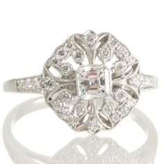 An Art Deco style platinum plaque engagement or dress ring featuring a central 0.26ct asscher cut diamond. View our collection of antique, Art Deco, and modern diamond rings at www.rutherford.com.au