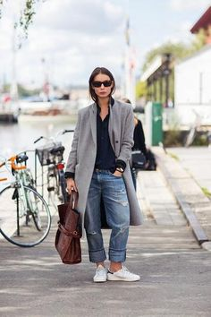 Fall Outfit Inspiration: Long gray coat worn with distressed boyfriend denim, chic leather bag, and white Adidas sneakers.