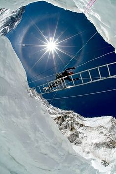 Crossing a crevasse in the Khumbu Icefall, metres ft) on the Nepali slopes of Mount Everest not far above Base Camp and southwest of the summit. The icefall is regarded as one of the most dangerous stages of the South Col route to Everest's summit.