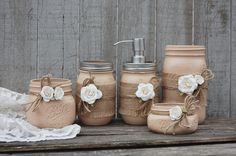 Shabby chic mason jar bathroom set. Hand painted in coffee brown, wrapped in burlap, tied with jute and cream colored roses, finished with a protective coating. Metal soap dispenser, toothbrush holder