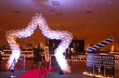 Walk thru star balloon arch with white lights and up lights. Complete with red carpet and stanchions.