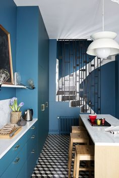 Antonin Roy's Parisian apartment is a masterclass in letting the space speak for itself.  Kitchen cabinet's in Farrow and Ball's Stiffkey Blue contrasts against marble workstop and house simple clear glass and caged lights