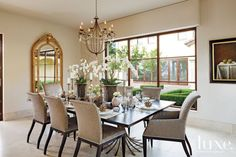A BEAUTIFUL TRANSITIONAL DINING ROOM IN A NEUTRAL COLOR SCHEME. THE CHANDLER AND ARCHED GOLD MIRROR ARE  GREAT CHOICES AND ADD INTEREST TO THE ROOM. THE LIGHTING FROM THE CHANDLER AND ITS LIGHTING REFLECTING FROM THE MIRROR ADDS A BEAUTIFUL AMBIANCE TO ALL THE DINNER PARTIES THE HOMEOWNERS HAVE. CHERIE