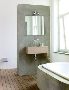 A concrete tub surround & wall, paired with a wood floor, in a bath spotted at Taverne Agency