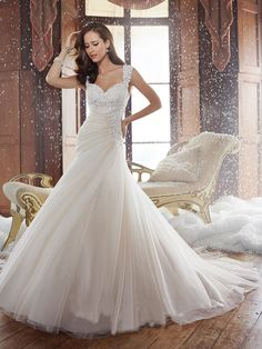 The Sophia Tolli Y21508 Sidney wedding dress is a fit and flare gown featuring a Guipure lace bodice and a layered tulle skirt that cascades to the ground with a chapel train. Tip-of-the-shoulder cap sleeves frame the sweetheart neckline and the cutout back. From the asymmetrical drop waist, the sumptuous skirt is gathered over one side, complemented by those converging around the corset back.