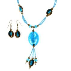 A distinctive blue beaded necklace and earring set, great for parties.  A large, central, glistening blue cabochon hung from a beaded necklace with feature asymmetric blue glass beads with a coppery gold finish.  The same asymmetric beads make up the complementary drop earrings presented on shepherd hooks suitable for pierced ears. Handmade in West Bengal, India. Only £17.99