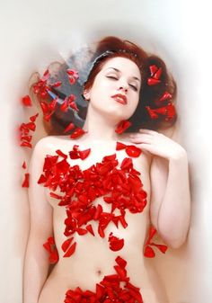 Redhead in bath with red flower petals…