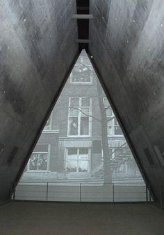 """Яд Вашем. Музей истории Холокоста. На входе в Музей посетителя встречает короткометражный фильм Михаль Ровнер """"Мир, которого больше нет"""" о жизни евреев в Европе накануне Шоа. Фильм демонстрируется на экране, выполненном в форме равнобедренного треугольника: его основание составляет 13 метров, высота – 11 метров. Продолжительность фильма – 10 минут"""