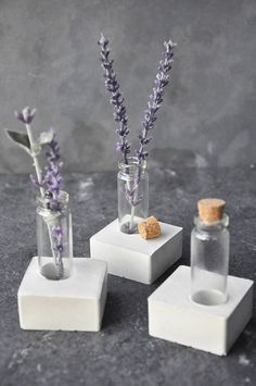 Mini Concrete Vase Add the perfect amount of nature to your desk, entryway, or bedroom. This mini concrete vase is a great combination of feminine and masculine elements. The base is a solid concrete square (2x2 x .5H) with a glass cylinder (roughly 2.5H) and a cork stopper. *Due