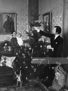 Queen Silvia is holding her daughter Victoria, 5 months old, while her husband King Carl Gustaf is decorating the Christmas tree on December 16, 1977 in Stockholm, Sweden.