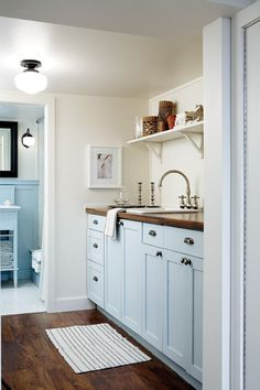 Bright Basement Laundry Room Pretty blue cabinets, dark-wood floors and a school-house light create an air of vintage charm. Blue Laundry Rooms, Laundry Room Colors, Room Paint Colors, Laundry Room Design, Mud Rooms, Small Laundry, Kitchen Colors, Man Cave Flooring Ideas, Basement Laundry